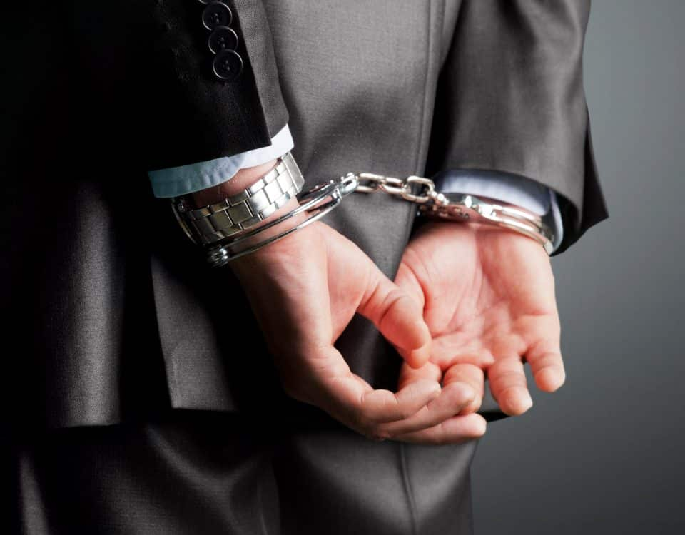 suited man's hands in handcuffs